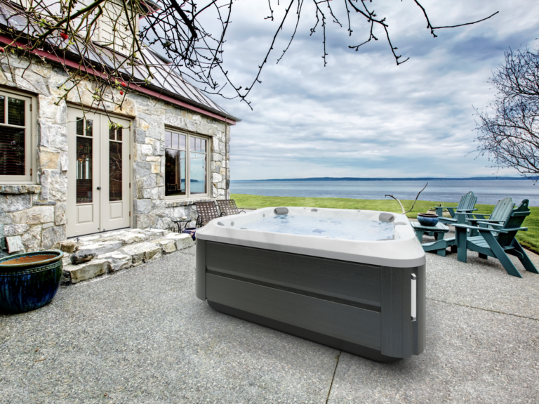 Jacuzzi Hot Tub installed outside by the water on a patio.